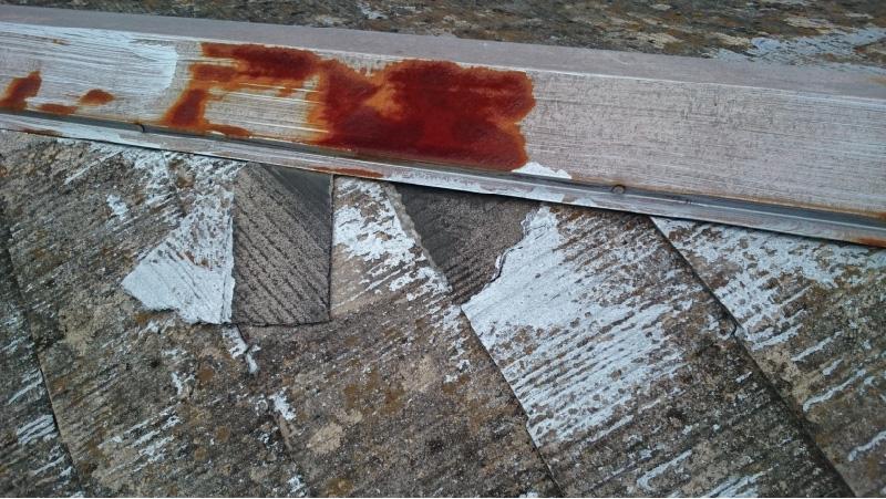 錆びた棟板金と割れたスレート瓦